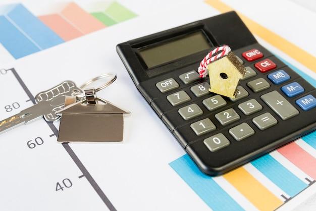 Birdhouse minuscule sur la calculatrice et porte-clés de maison sur le graphique