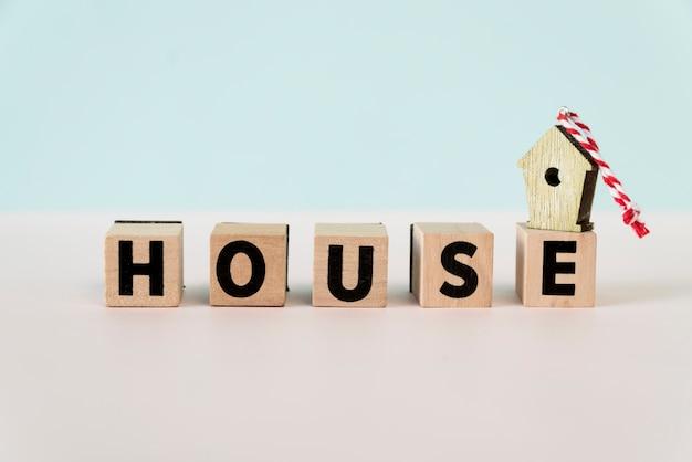 Birdhouse ornements sur bloc de maison en bois sur fond bleu