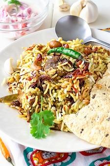 Biryani indien avec accompagnements, ail et piment