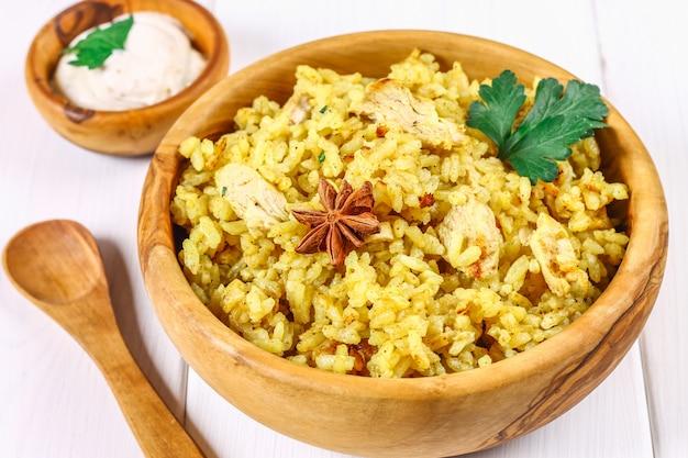 Biryani indien avec poulet, yaourt, assiette d'épices sur une table en bois. nouvel an, plat de noël.
