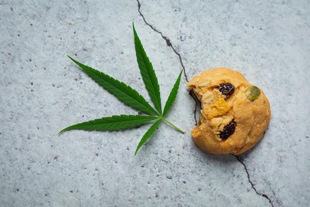 Biscuit au cannabis et feuille de cannabis posé sur le sol