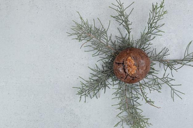 Un biscuit au chocolat aux noix sur une surface blanche