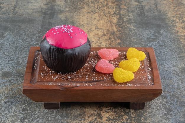 Biscuit au chocolat avec glaçage rose et bonbons sur planche de bois