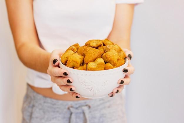 Biscuit au gingembre fait maison dans un plat profond dans les mains de la femme