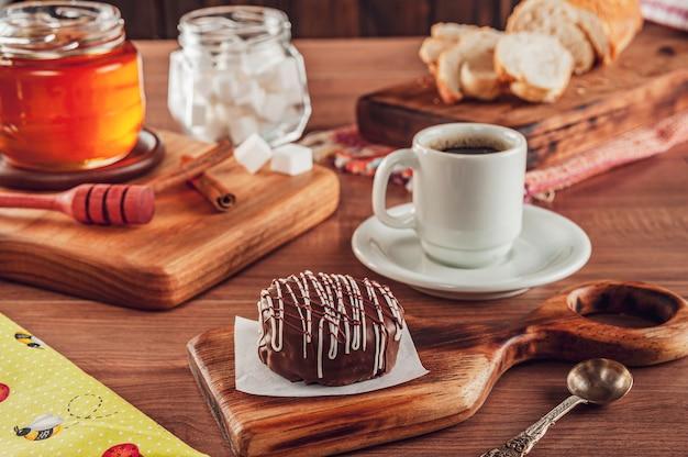 Biscuit au miel brésilien chocolat recouvert sur la table en bois avec café et abeille - pã £ o de mel
