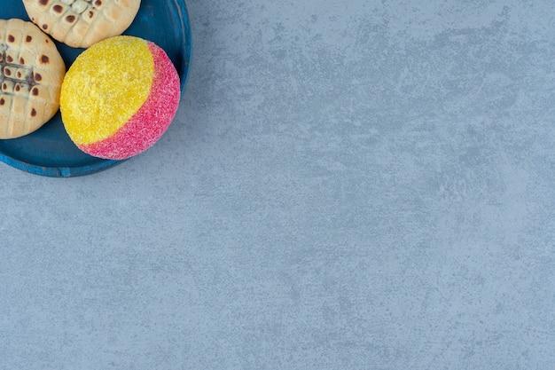 Biscuit aux pêches fraîches sur plaque bleue sur gris.