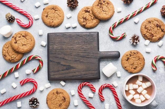 Le biscuit aux pépites de chocolat, cône de cacao et guimauve à la canne de noël, caramel cup décors sur fond gris. copyspace frame.