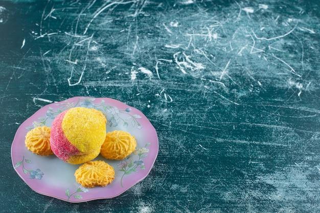 Biscuit et biscuits de deux couleurs sur une assiette colorée.