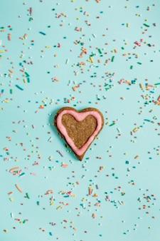 Biscuit et confettis de symbole de coeur coloré à la main sur bleu