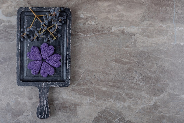 Biscuit dentaire et raisin sur le plateau, sur la surface en marbre