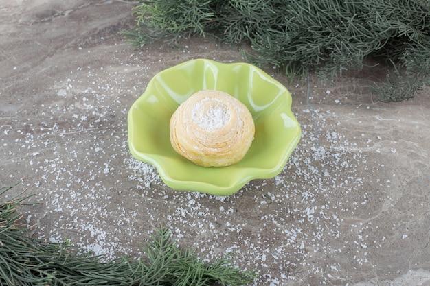 Biscuit feuilleté dans un petit bol entre des branches de pin sur une surface en marbre