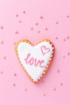 Biscuit en forme de coeur avec mot love sur fond rose