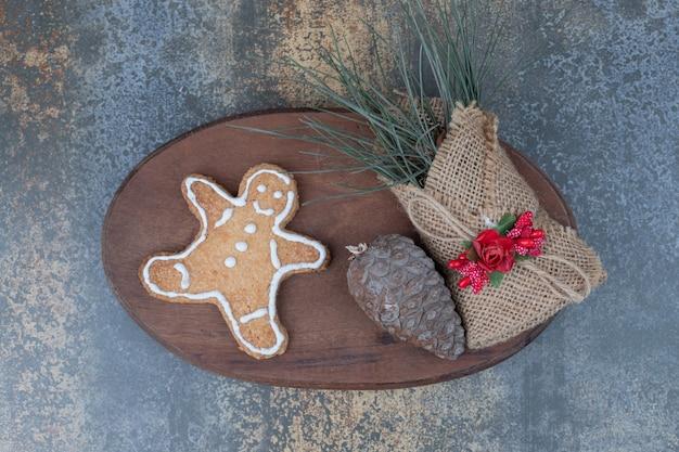 Biscuit homme en pain d'épice, pomme de pin et herbes en toile de jute sur plaque de bois. photo de haute qualité