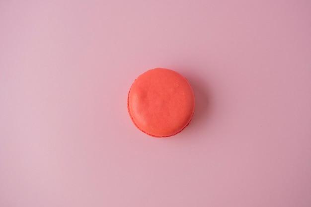 Un biscuit macaron est orange sur un fond de papier rose. minimalisme, dessert délicieux