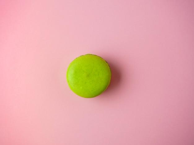Un biscuit macaron est vert sur un fond de papier rose. minimalisme, dessert délicieux