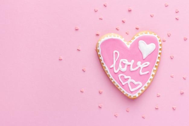 Biscuit maison avec mot amour et coeurs glacés avec du glaçage au sucre sur fond rose pour la saint-valentin ou le mariage