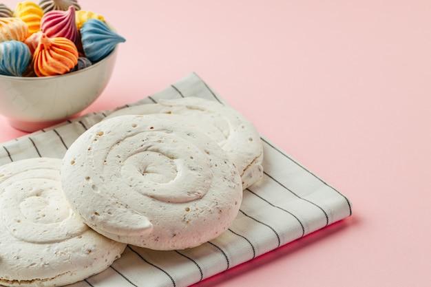 Biscuit meringue blanc sur fond rose avec des mini meringues colorées