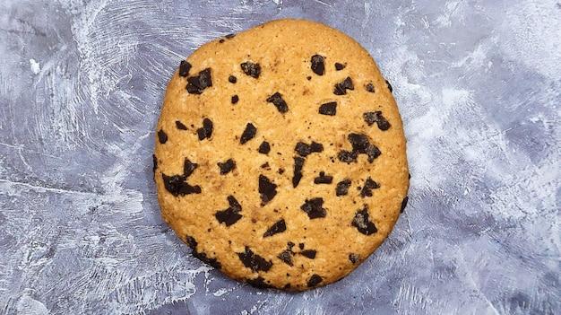 Un biscuit moelleux aux pépites de chocolat fraîchement sorti du four sur un comptoir de cuisine en marbre gris. pâtisserie traditionnelle américaine, dessert. délicieuse nourriture sucrée. mise à plat.