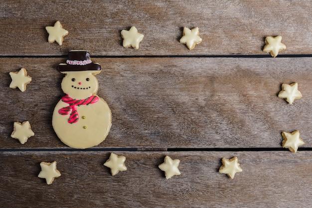 Biscuit de noël et nouvel an en forme de bonhomme de neige, flocon de neige, étoile sur une table en bois