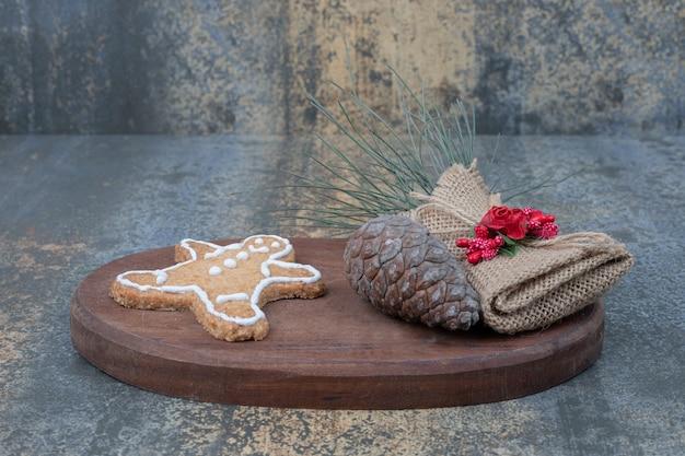 Biscuit de noël avec pomme de pin sur planche de bois.