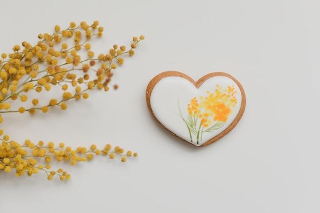 Biscuit de pain d'épice en forme de coeur et fleurs de mimosa sur fond blanc. espace copie vue de dessus