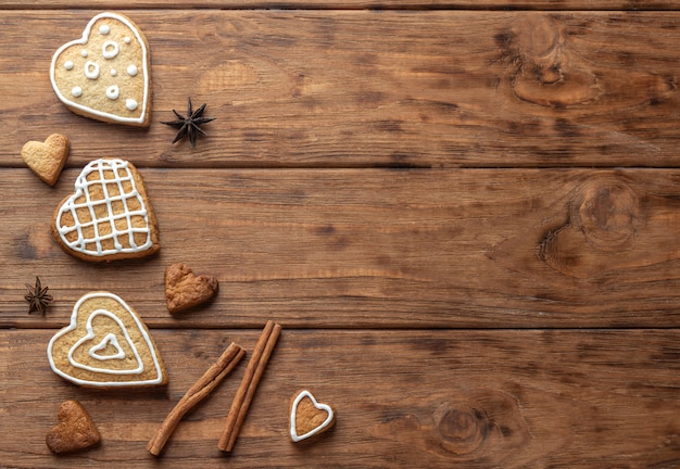 Biscuit de pain d'épice en forme de coeur avec glaçage sur fond de bois
