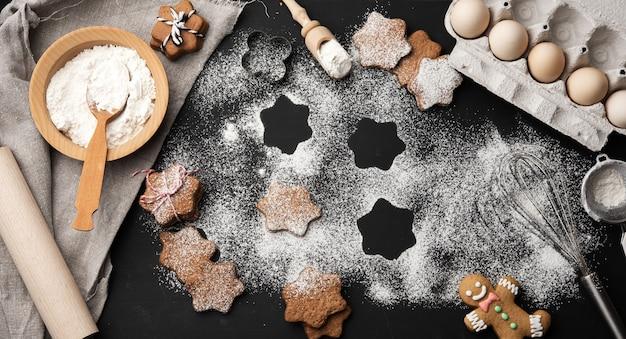 Biscuit de pain d'épice en forme d'étoile cuit au four saupoudré de sucre en poudre sur une table noire et ingrédients, vue du dessus
