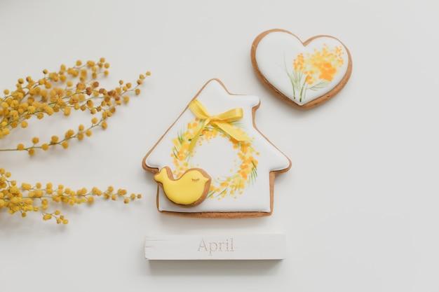 Biscuit de pain d'épice de pâques et fleur de mimosa sur fond blanc. printemps, printemps, avril, concept de joyeuses pâques. vue de dessus