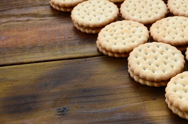 Biscuit sandwich fourré à la noix de coco repose en grande quantité sur une surface en bois brune