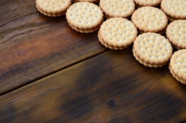 Un biscuit sandwich rond fourré à la noix de coco repose en grande quantité sur une surface en bois brune