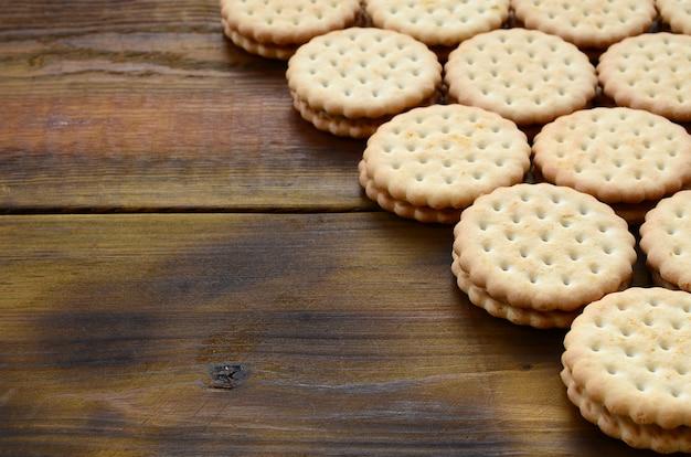 Un biscuit sandwich rond avec une garniture à la noix de coco repose en grande quantité sur une surface en bois brune. photo de friandises comestibles sur un fond en bois avec espace de copie