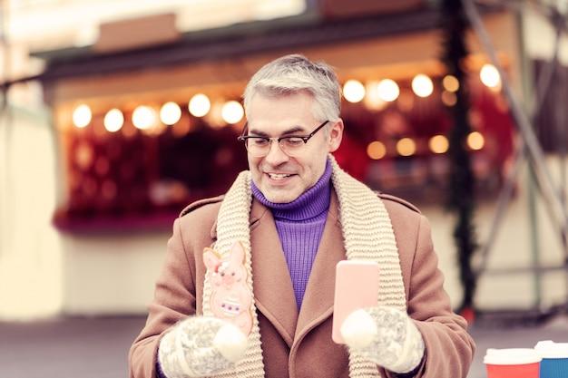Biscuit savoureux. gentil homme tenant le téléphone dans la main gauche et regardant la pâtisserie