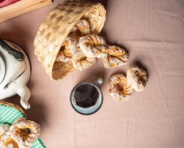 Biscuit sucré brésilien et une tasse de café sur une table avec nappe beige, mise au point sélective.