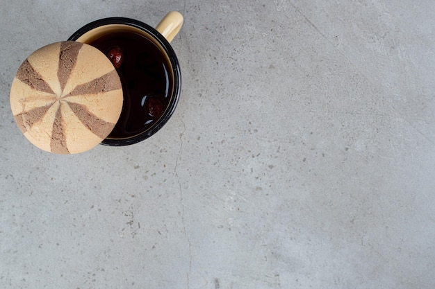 Biscuit sur une tasse de thé à la rose de chien sur une surface en marbre