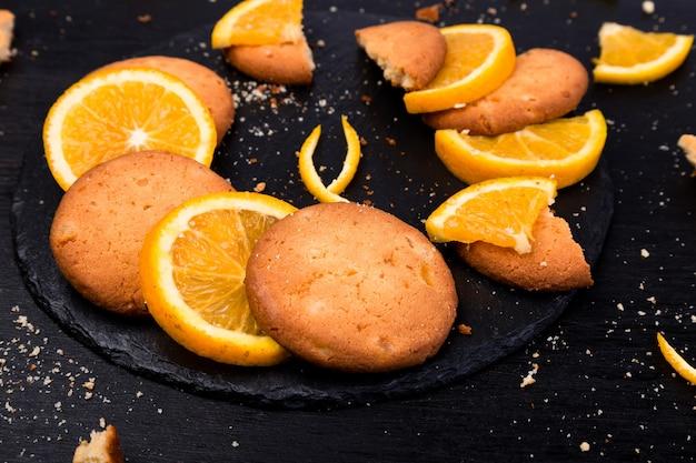 Biscuits et agrumes orange sur une plaque d'ardoise sur fond noir.