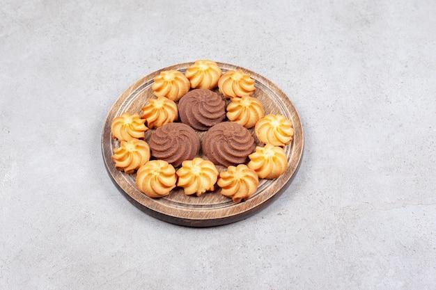 Biscuits alignés de façon décorative sur planche de bois sur fond de marbre. photo de haute qualité