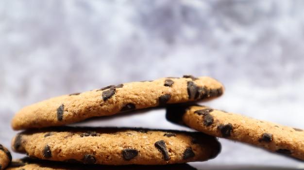 Biscuits américains aux pépites de chocolat empilés les uns sur les autres sur un beau fond de marbre gris. pâte croustillante arrondie traditionnelle aux pépites de chocolat. boulangerie. dessert délicieux, pâtisseries.