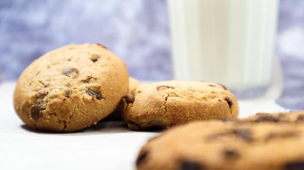 Biscuits américains aux pépites de chocolat sans gluten avec verre en verre de lait végétal sur fond gris. gâteaux avec des pépites de chocolat. pâtisseries sucrées, dessert. contexte culinaire.
