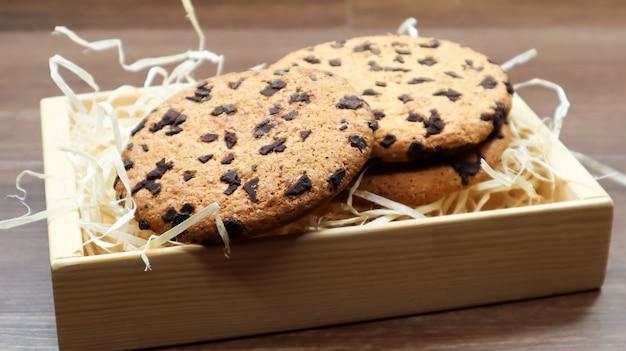 Biscuits américains aux pépites de chocolat sur une table en bois marron close-up dans une boîte. pâte croustillante arrondie traditionnelle aux pépites de chocolat. boulangerie. dessert délicieux, pâtisseries. nature morte rurale.