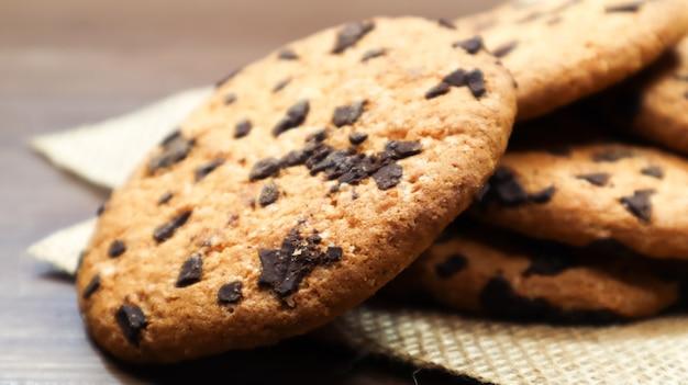 Biscuits américains aux pépites de chocolat sur une table en bois marron et sur un gros plan de serviette en lin. pâte croustillante arrondie traditionnelle aux pépites de chocolat. boulangerie. dessert délicieux, pâtisseries. nature morte rurale.