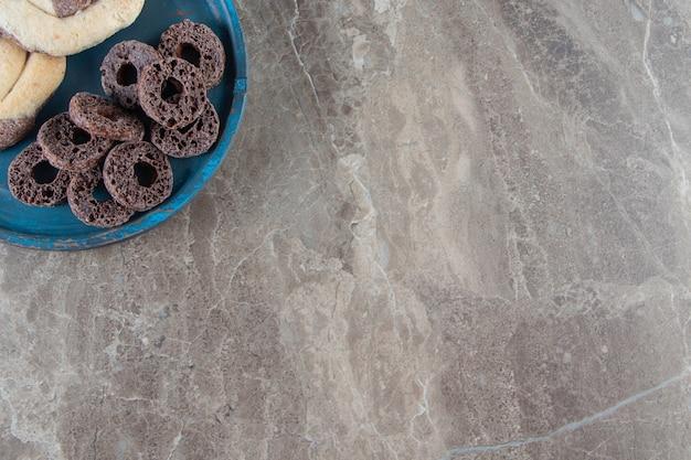 Biscuits et anneaux de maïs sur une plaque en bois sur marbre.