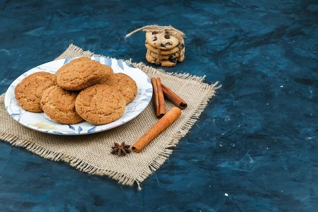 Biscuits sur une assiette aux épices, bâtons de cannelle