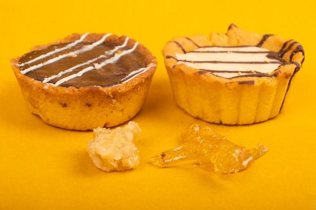 Biscuits au cannabis, aliments sucrés à l'huile de haschich sur fond jaune.
