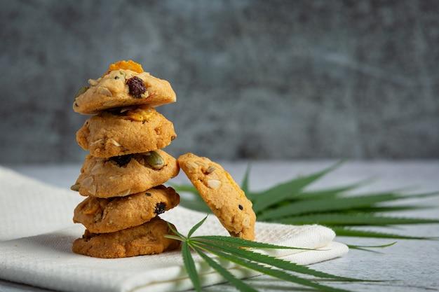 Biscuits au cannabis et feuilles de cannabis mis sur une serviette blanche