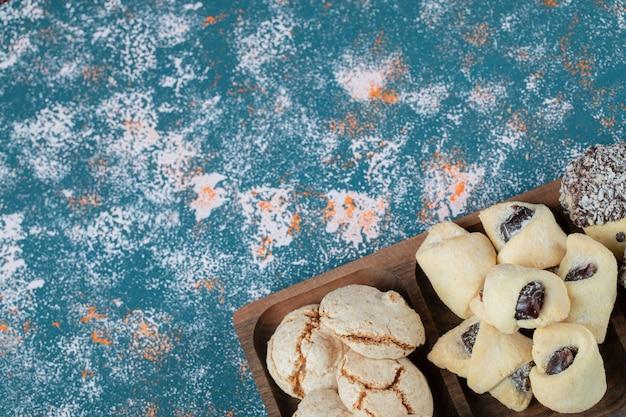 Biscuits au chocolat et au beurre dans une planche de bois carrée.