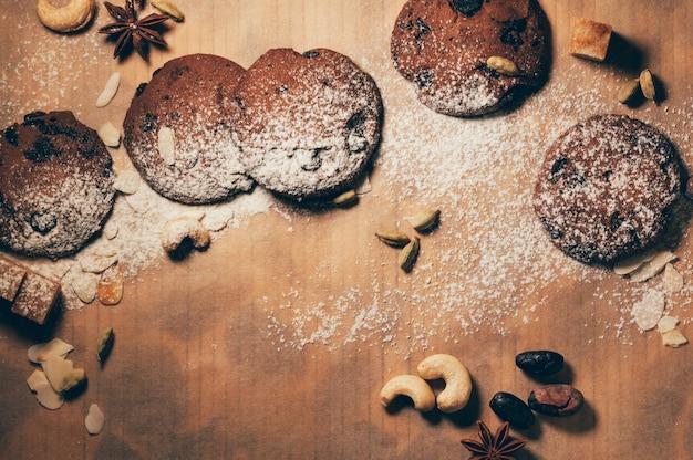 Biscuits au chocolat aux épices, noix et farine sur table