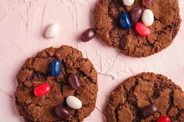 Biscuits au chocolat d'avoine fait maison avec des céréales avec des fèves à la gelée juteuse sur la surface rose texturée, vue de dessus macro
