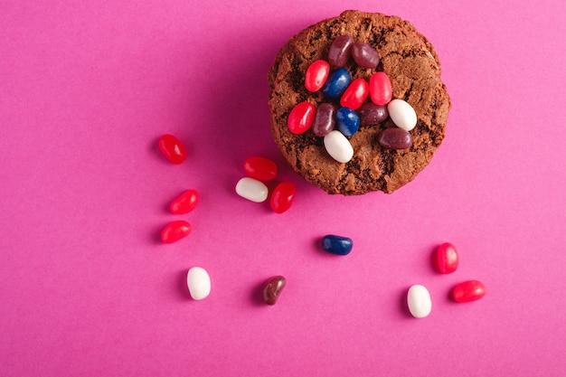 Biscuits au chocolat à l'avoine fait maison pile avec des céréales avec des fèves à la gelée juteuse sur fond rose violet minimal, vue de dessus