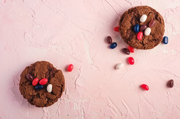 Biscuits au chocolat à l'avoine faits maison avec des céréales avec des fèves à la gelée juteuse sur fond rose texturé, vue de dessus copie espace