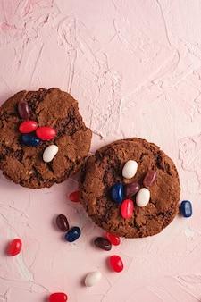 Biscuits au chocolat à l'avoine faits maison avec des céréales avec des fèves à la gelée juteuse sur un mur rose texturé, vue de dessus copie